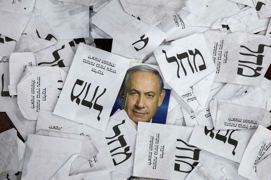 Ballots and campaign posters for Israel's Prime Minister Benjamin Netanyahu  lie on the ground, perhaps symbolizing his diplomat-ic problems. Photo: JACK GUEZ, Staff / AFP