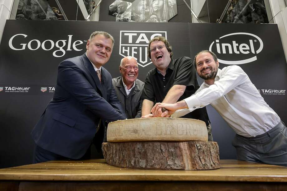 (L TO R) Swiss watchmaker Tag Heuer Director General Guy Semon, Tag Heuer CEO Jean-Claude Biver, Intel's new device general manager Michael Bell and Google's engineering director for Android wear David Singleton pose with a Swiss cheese during the anoucement on March 19, 2015 in Basel of a partnership between the watch brand, owned by the French luxury group LVMH and the two giants of the Silicon Valley. Luxury Swiss watchmaker Tag Heuer announced  it was joining forces with technology behemoths Google and Intel to develop a connected timepiece that can compete with the new Apple Watch.AFP PHOTO / FABRICE COFFRINIFABRICE COFFRINI/AFP/Getty Images Photo: Fabrice Coffrini, AFP / Getty Images