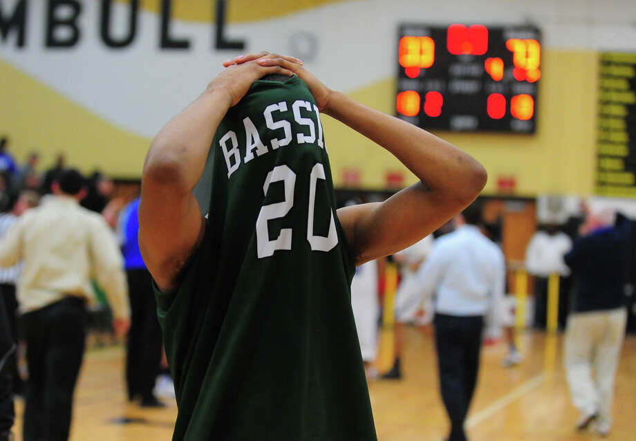 Bassick's Jarod Hamilton covers his head as he leaves the court after the team was beat by one point, during Class L boys basketball semifinal action against Bunnell in Trumbull, Conn., on Thursday Mar. 19, 2015. Photo: Christian Abraham / Connecticut Post