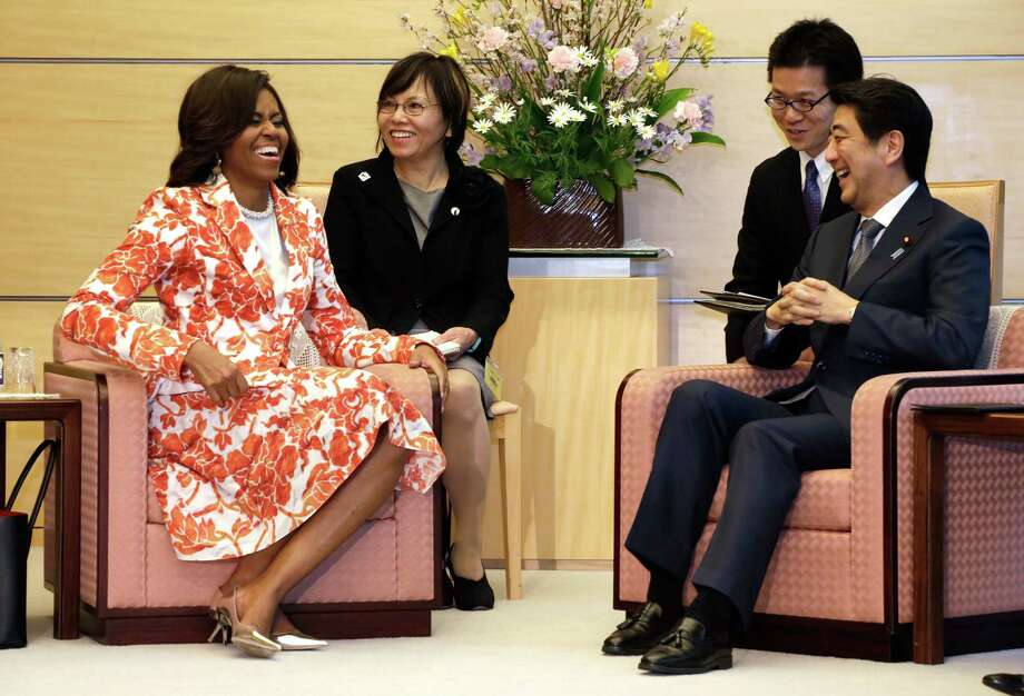 """First lady Michelle Obama enjoys a cordial meeting with Japanese Prime Minister Shinzo Abe, right, as she promotes """"Let Girls Learn."""" Photo: Eugene Hoshiko, STF / AP"""