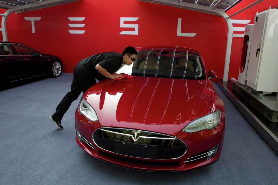 A worker cleans a Tesla Model S sedan. Tesla's latest update will map out the best route to a driver's destination based on the location of charging stations.  Photo: Ng Han Guan, STF / AP