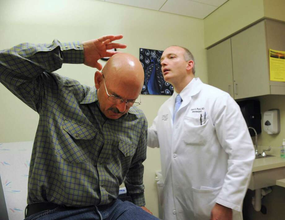 University of Texas Health Science Center at San Antonio neurosurgeon John R. Floyd II looks at the back of cancer patient David Williams' head during an exam in March. Williams, 54, of Natalia, is the first person in the world to have a radiation treatment implant put directly into his brain. The technology, which emits tiny radioactive liposomes, or fat particles, was implanted with the help of a tiny catheter. The novel treatment is now part of a clinical trial taking place at the university's Cancer Therapy & Research Center. Photo: Express-News File Photo / San Antonio Express-News