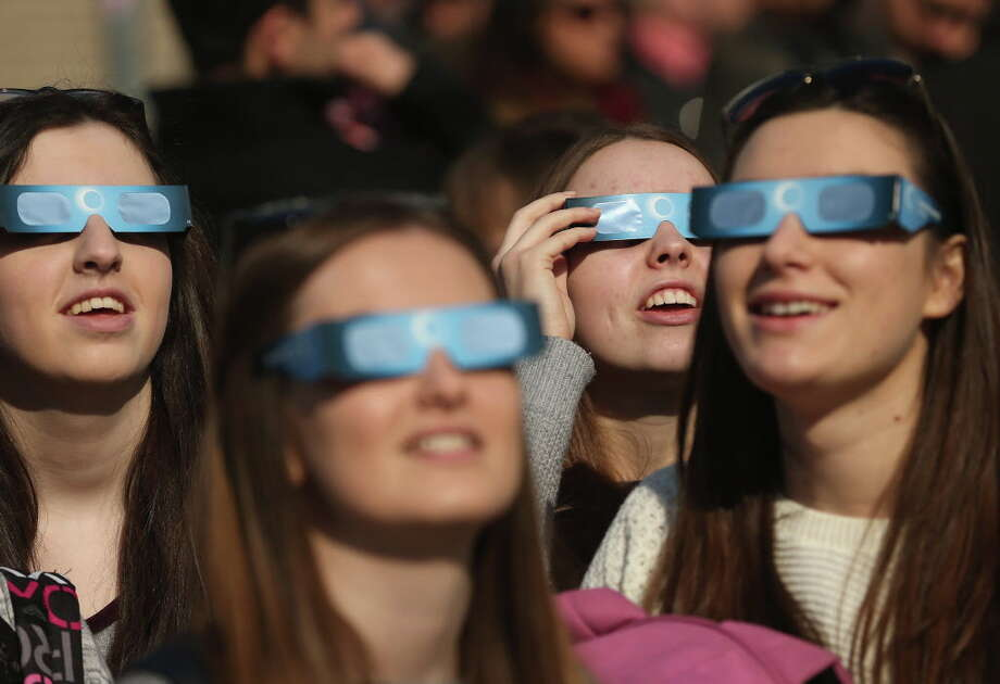 FILE--  People use special glasses to look into the sky at a partial solar eclipse near the Brandenburg Gate on March 20, 2015 in Berlin, Germany. Many within the cannabis community have mobilized to make the most of the August 21 total eclipse of the sun, visible in the United States for the first time since February 1979. Photo: Sean Gallup / 2015 Getty Images