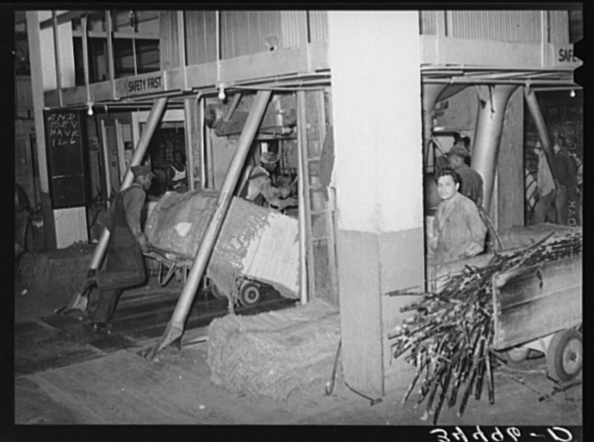 October 1939 : Placing a bale of cotton into compressing unit in Houston.