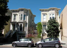 These two houses on the 2500 block of Clay Street, just east of Alta Plaza, were built as part of a housing tract in 1874 -- and aren't quite as substantial as they appear from the front, since the cornice extends several feet above the roof.