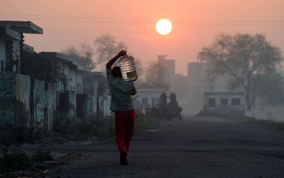 A migrant laborer carrys a bottle of water he filled from a water tanker at a camp where he and others like him live in New Delhi.