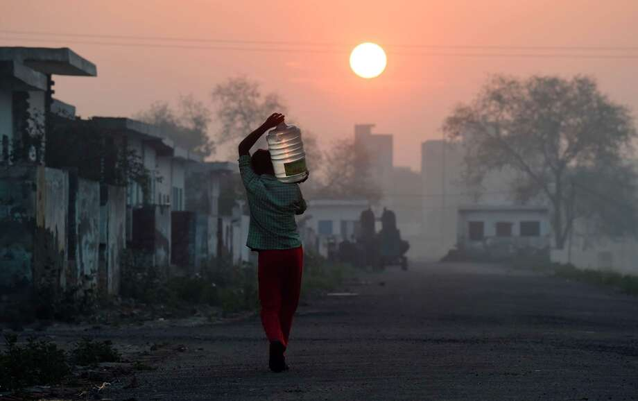 A migrant laborer carrys a bottle of water he filled from a water tanker at a camp where he and others like him live in New Delhi. Photo: ROBERTO SCHMIDT / AFP / Getty Images / AFP