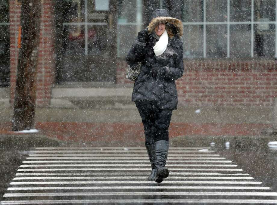 Roberta Schreiber, of Fairfield, pulls her hood down to block the blowing snow as she crosses Post Road in Fairfield Friday, Mar. 20, 2015. Photo: Autumn Driscoll / Connecticut Post