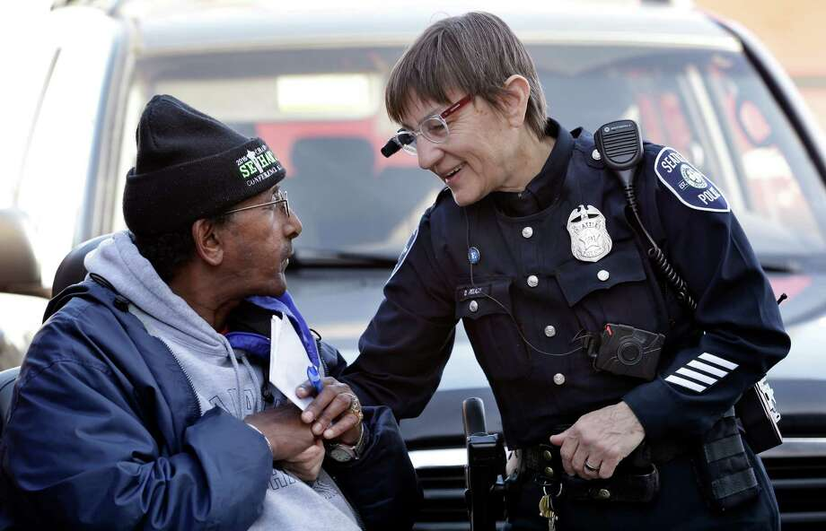 Seattle officer Debra Pelich wears a camera on her eyeglasses as she talks with Alex Legesse. Photo: Elaine Thompson / Associated Press / AP