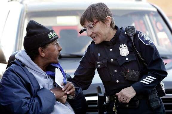 Seattle officer Debra Pelich wears a camera on her eyeglasses as she talks with Alex Legesse.