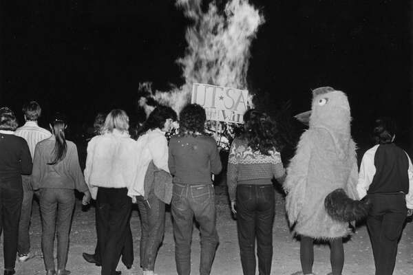 UTSA students and the Roadrunner warm-up with the homecoming bonfire.
