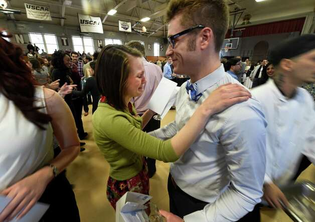 Amy Spallone, with tears of joy gets a hug from Keith Sweeney after opening  their envelopes containing the key to their future hospital assignments Friday afternoon March 20, 2015 on Matching Day in Albany, N.Y. They both received assignments at Stony Brook Teaching Hospital in Stony Brook, N.Y.  The process matches graduating medical school students with a residency program where they will complete their medical specialty training. (Skip Dickstein/Times Union) Photo: SKIP DICKSTEIN / 10031117A