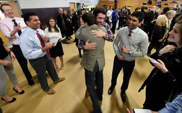 Nick Richardson gets a hug from Jake Oberwetter, foreground,  after they received their hospital assignments Friday afternoon March 20, 2015 on Matching Day in Albany, N.Y. The process matches graduating medical school students with a residency program where they will complete their medical specialty training. (Skip Dickstein/Times Union) Photo: SKIP DICKSTEIN / 10031117A