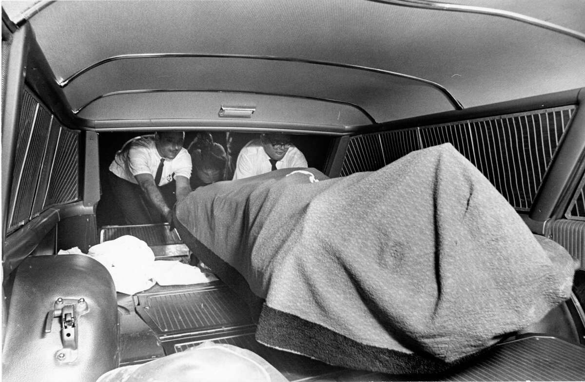 06/1965 - The bodies of murdered couple are loaded into medical examiner's vehicle for transport. Fred C. Rogers, 81, and his wife, Edwina Harmon Rogers, 79, were dismembered and found in the refrigerator in their home at 1815 Driscoll on June 23, 1965.