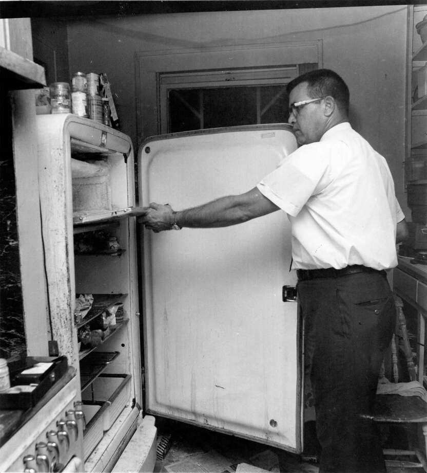 Houston Police homicide detective J.P. Paulk examines the freezer compartment of a refrigerator where a torso was found. Fred C. Rogers, 81, and his wife, Edwina Harmon Rogers, 79, were found dismembered in their refrigerator at 1815 Driscoll on June 23, 1965. Photo: Bill Goodwin, Houston Chronicle / Houston Post files