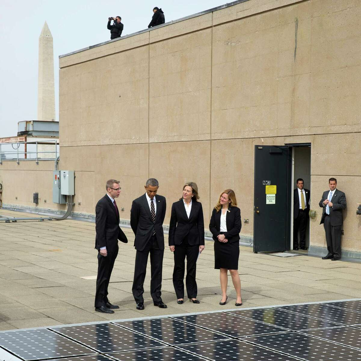 President Obama views solar panels on the roof at the Department of Energy headquarters in Washington on Thursday. Obama signed an executive order cutting the federal government's greenhouse gas emissions. From left: Eric Haukdal, an energy manager at the DOE, Obama, Deputy Energy Secretary Elizabeth Sherwood-Randall and Kate Brandt, the federal environmental executive.
