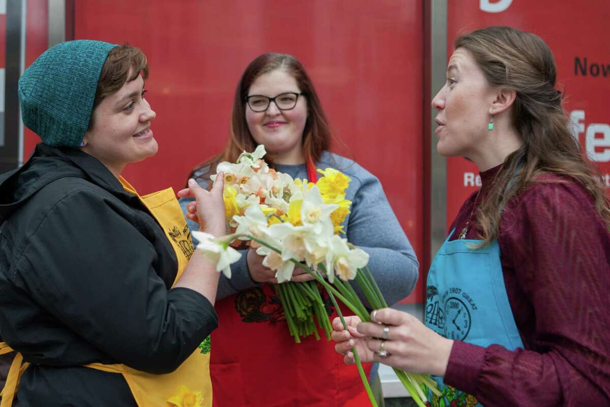 Volunteers Megan Carlisle and Natalie Hammers from Nature's Twist at Pike Place Market hand out free daffodils downtown with another volunteer, Stacy Gilbert. Volunteers handed out a total of 9,000 daffodils in celebration of the first day of spring. Photo taken on March 20, 2015.