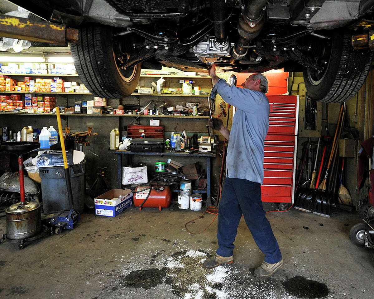 Kola Papaj works on a customer's car while it is up on a lift at A&K Service in Stamford, Conn., on Tuesday, March 10, 2015.