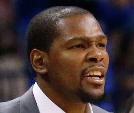 Injured Oklahoma City Thunder forward Kevin Durant reacts on the bench to a basket in the fourth quarter of an NBA basketball game against the Toronto Raptors in Oklahoma City, Sunday, March 8, 2015. Oklahoma City won 108-104. (AP Photo/Sue Ogrocki)