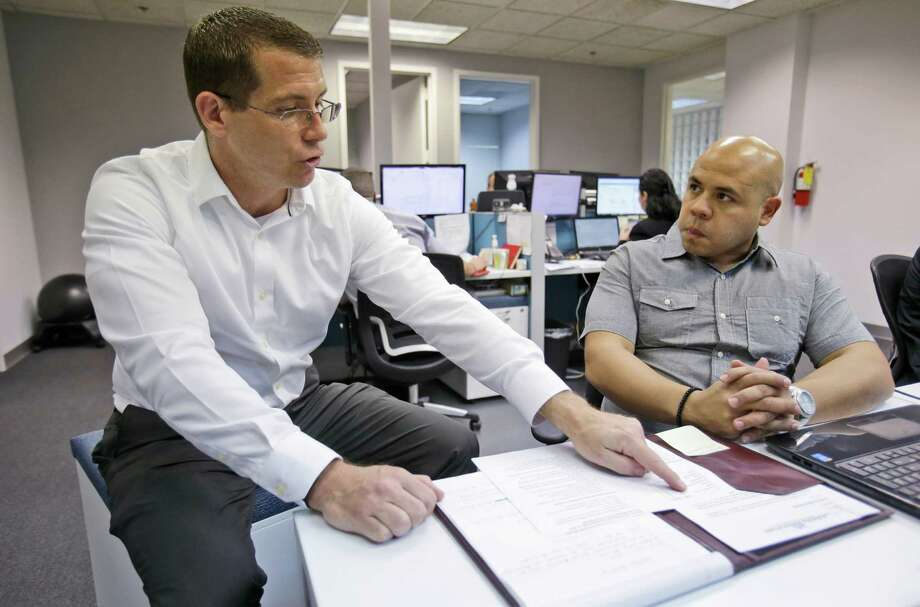 Brad Mete, a managing partner at Affinity Resources, a temporary staffing company, left, helps new recruiter Obed Blanco on his first day at work in Miami Lakes, Fla. Complying with the Affordable Care Act will cost his firm $100,000. Photo: Wilfredo Lee, STF / AP