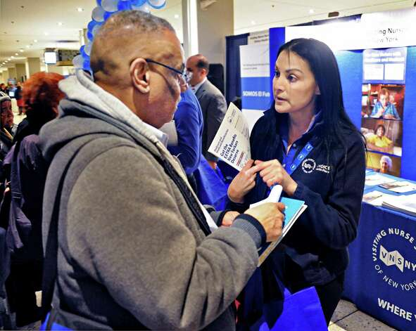 Juan Melendez, left, of NYC gets some information from Elizabeth Ruix of the Visiting Nurse Service of NY during Somos el Futuro Spring 2015 Conference in the Empire State Plaza Friday March 20, 2015 in Albany, NY.   (John Carl D'Annibale / Times Union) Photo: John Carl D'Annibale / 00031126A