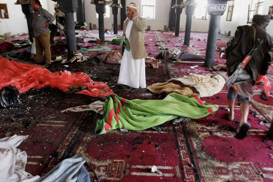 Bodies are covered with blankets in a mosque after a suicide attack killed dozens during the noon prayer Friday in Sanaa, Yemen. Photo: Hani Mohammed, STR / AP