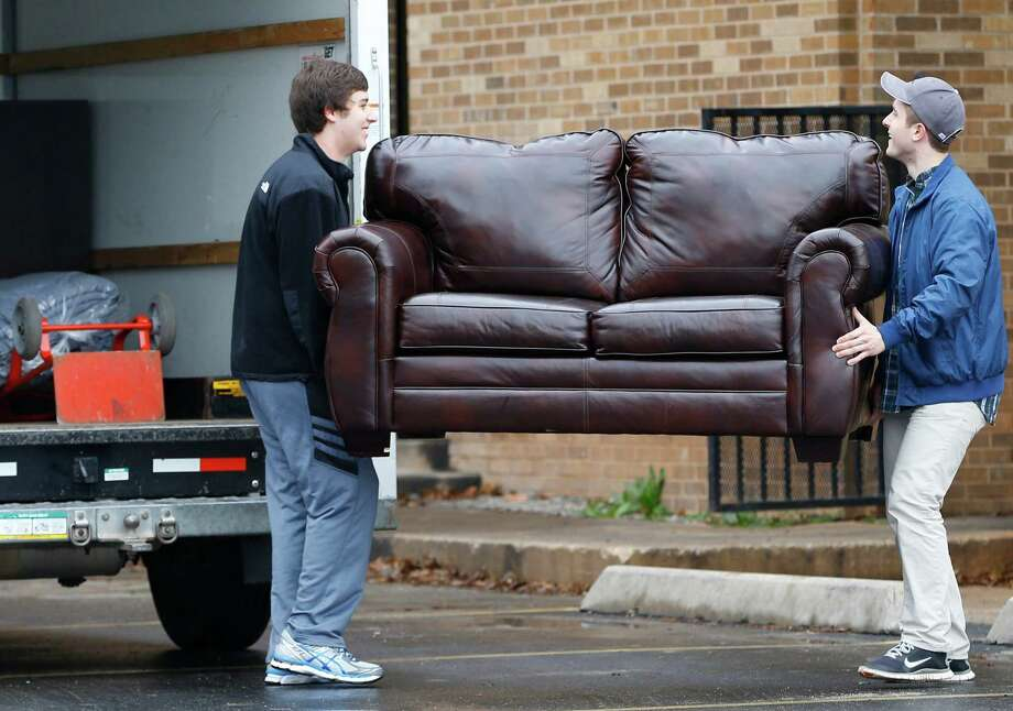 File-This March 10, 2015, file photo shows two men loading a couch from the now closed University of Oklahoma's Sigma Alpha Epsilon fraternity house into a moving truck, in Norman, Okla. Fraternities dominate social life at many American universities, but lately these organizations of male college students have been receiving unwanted attention for their bad behavior. At the University of Oklahoma, one prominent fraternity was shut down after members were caught on video performing a racist chant. (AP Photo/Sue Ogrocki, File) Photo: Sue Ogrocki, AP / AP