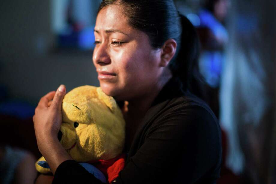 Raquel Reyes hugs her older son's stuffed animal while trying to come to terms with his tragic death. Photo: Marie D. De Jesus, Staff / © 2015 Houston Chronicle