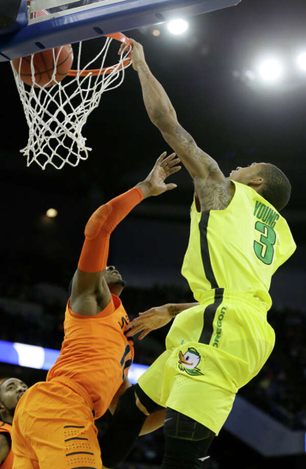 Joseph Young dunks over Oklahoma State's Anthony Hickey. Photo: Charlie Neibergall / Associated Press / AP