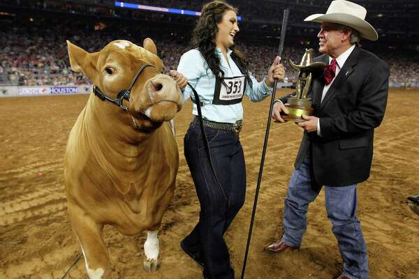 Caitlen Hope Doskocil of Holland FFA in Buckholts accepts the award for her grand champion steer, Peaches, on Friday during the Houston Livestock Show and Rodeo at NRG Stadium.