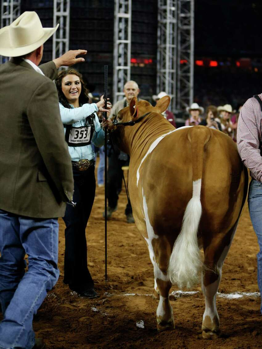 A judge arrives to slap the rear end of Peaches as the steer is named the top winner at the rodeo.