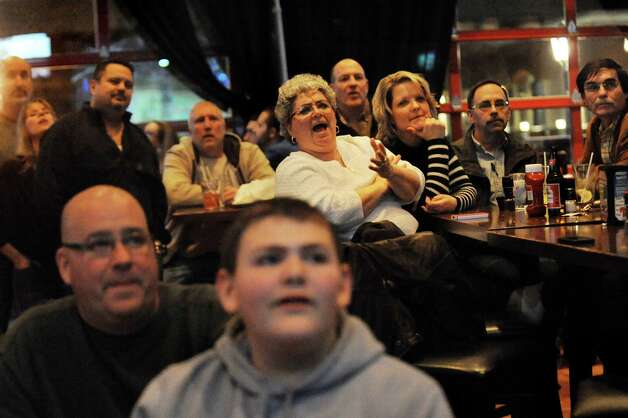 Connie Simpson of Slingerlands, center, react to a play when UAlbany plays Oklahoma in the NCAA Tournament on the big screen on Friday, March 20, 2015, at Wolf's 111 in Colonie, N.Y. (Cindy Schultz / Times Union) Photo: Cindy Schultz / 00031129A