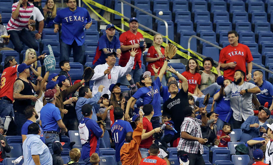 Baseball fans reach for a home run hit by Los Angeles Dodgers' Joc Pederson during the Big League Weekend spring exhibition baseball game against the Texas Rangers held Friday March 20, 2015 at the Alamodome. Photo: Edward A. Ornelas /San Antonio Express-News / © 2015 San Antonio Express-News