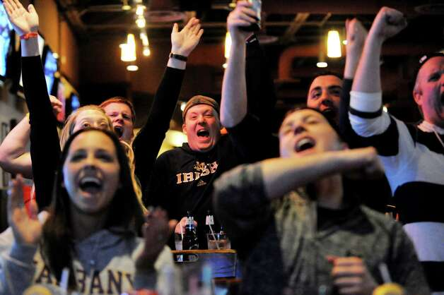 UAlbany Alumus Kevin O'Rourke, center, joins fans in cheering a play as UAlbany plays Oklahoma in the NCAA Tournament on the big screen on Friday, March 20, 2015, at Wolf's 111 in Colonie, N.Y. (Cindy Schultz / Times Union) Photo: Cindy Schultz / 00031129A