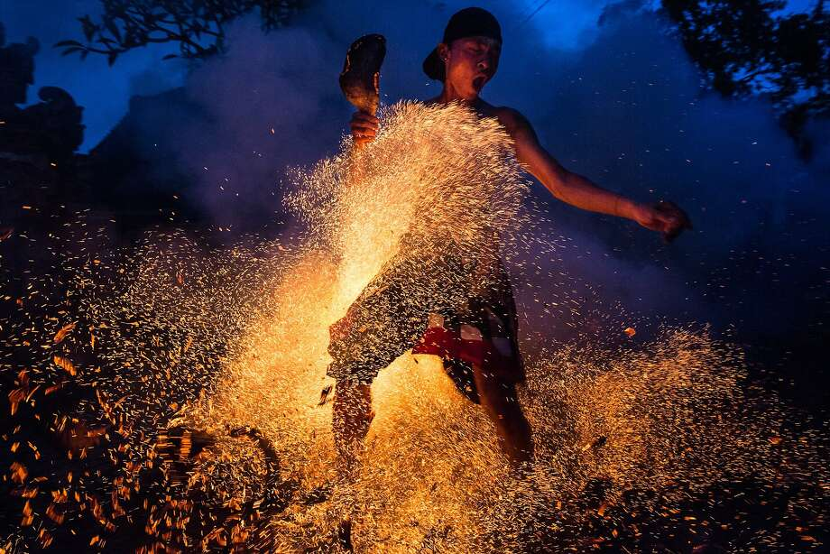 "A Balinese man kicks up the fire during the ""Mesabatan Api"" ritual ahead of Nyepi Day on March 20, 2015 in Gianyar, Bali, Indonesia. Mesabatan Api is held annually a day before the Nyepi Day of Silence, as it symbolizes the purification of universe and human body through fire. Nyepi is a Hindu celebration observed every New Year according to the Balinese calendar. The national holiday is one of self-reflection and meditation and activities such as working, watching television or travelling are restricted between the hours of 6 a.m. and 6 p.m. Photo: Agung Parameswara"