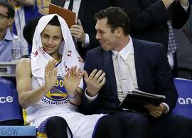 Golden State Warriors' Stephen Curry, left, jokes with assistant coach Luke Walton after a dunk from teammate Andre Iguodala during the second half of an NBA basketball game against the New Orleans Pelicans, Friday, March 20, 2015, in Oakland, Calif. (AP Photo/Marcio Jose Sanchez)