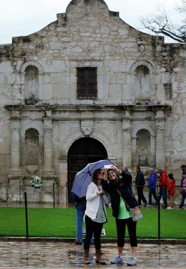 """Cousins Sydney Vernon (right) and Jennifer Goodwin from South Carlolina take a """"selfie"""" in front of the Alamo before going on a tour on Saturday, Mar. 21, 2015. Light to moderate rain fell overnight and weather officials warned the area for possible urban and small stream flooding. (Kin Man Hui/San Antonio Express-News) Photo: Kin Man Hui, By Kin Man Hui/San Antonio Express-News / ©2015 San Antonio Express-News"""