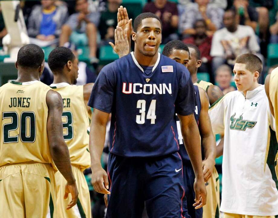 Connecticut's Alex Oriakhi reacts as South Florida players, including Dominique Jones (20) celebrate late in the second half of their 75-68 win in an NCAA college basketball game Saturday, March 6, 2010, in Tampa, Fla. (AP Photo/Mike Carlson) Photo: Mike Carlson, ASSOCIATED PRESS / AP2010