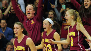 St. Joseph's coach Chris Lindwall and his team react as they beat Cromwell, during CIAC State Girls Basketball Tournament action at Mohegan Sun in Uncasville, Conn., on Saturday Mar. 21, 2015.