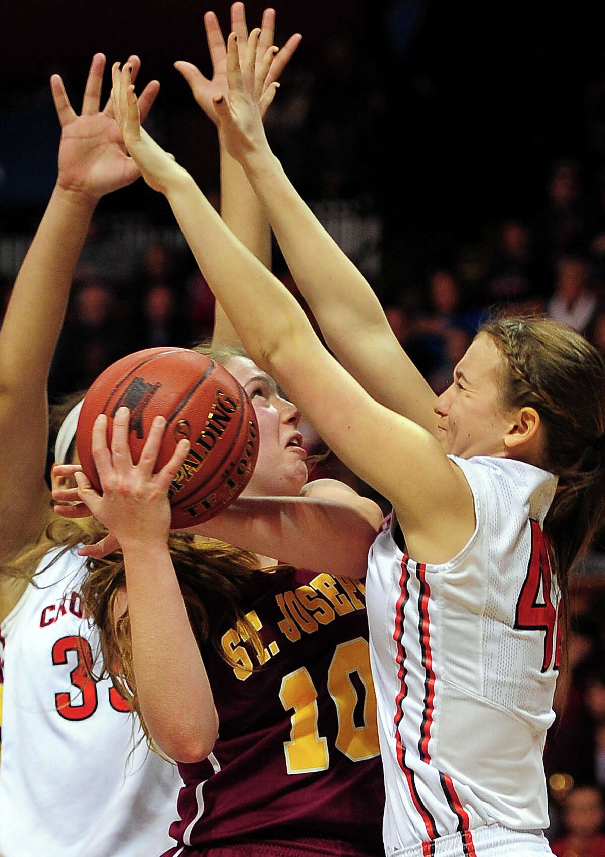 St. Joseph's Bridget Sharnick gets sandwiched between Cromwell players Geanna Williams, left, and Theresa Quinn, right, during CIAC State Girls Basketball Tournament action at Mohegan Sun in Uncasville, Conn., on Saturday Mar. 21, 2015.