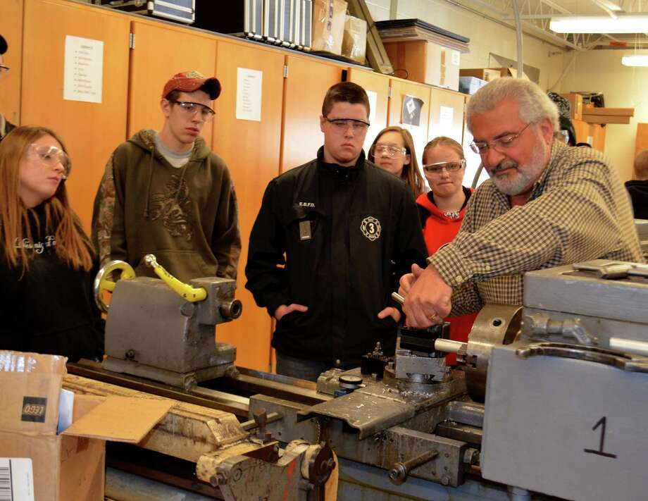 Eighteen students from three area high schools took part in a tour Thursday of two local employers, Package One Industries in Scotia and Simmons Tool Company in Watervliet. The students from Cohoes, Mohonasen and Berne-Knox-Westerlo took part in a manufacturing and machining open house and tour. During the daylong event, they learned about careers that offer advancement opportunities and good pay and the potential for a free college education. Students later went to Mohonasen High School to tour the Capital Region BOCES Career and Technical Education (CTE) Machining Program and hear from other industry experts. Here, retired teacher Mike Saredella shows how to use equipment at the CTE. (Photo provided by Mike McCagg)