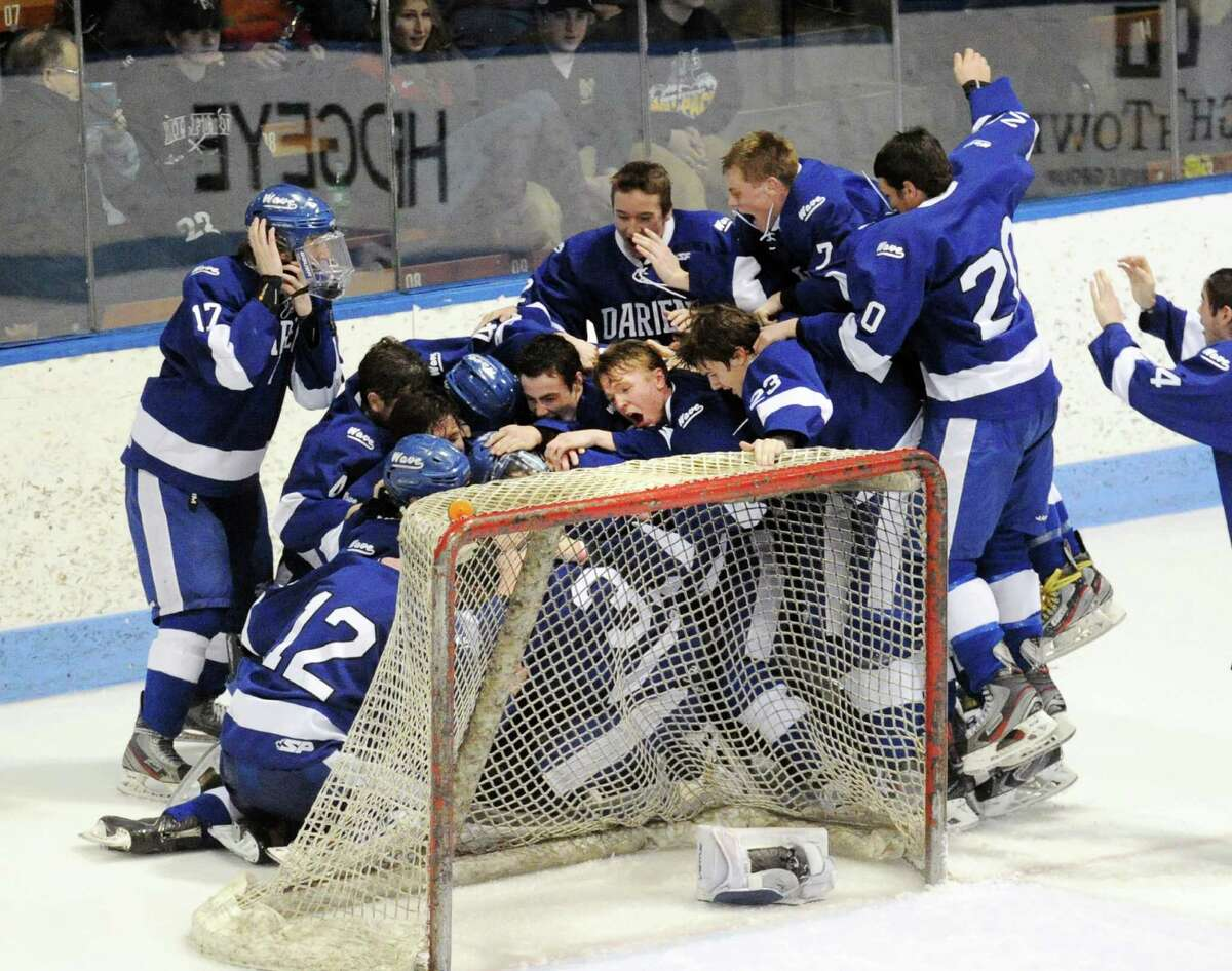 The Darien High School boys hockey team celebrates their 1-0 CIAC Division I boys state hockey championship victory over Greenwich High School at Ingalls Rink in New Haven, Conn., Saturday March 21, 2015. Darien took the title with a 1-0 victory over Greenwich on a Jack Pardue goal in the second period.
