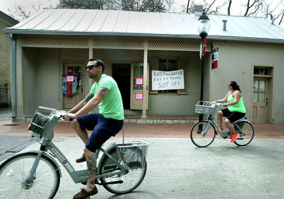 Tourists ride bikes past Lone Star Mercantile in La Villita, which shows a sign that they lost their lease with the city. Photo: Bob Owen /San Antonio Express-News / © 2015 San Antonio Express-News