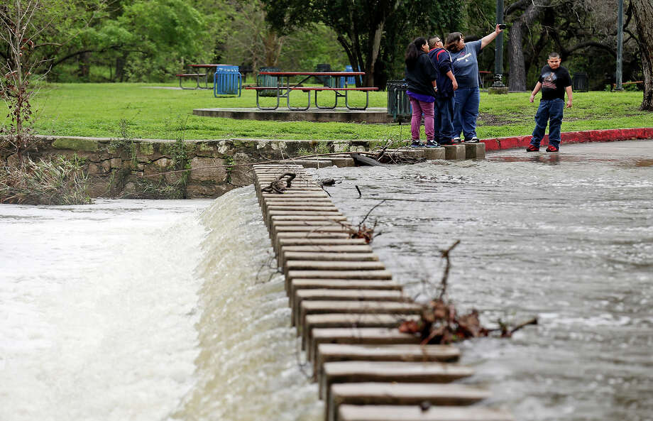 Katrina Vega, (from left) Ethan Vega, and Susie Gonzalez pose for a photo at the low water crossing in Brackenridge Park as Alonzo Gonzalez looks on as storms move through the area Saturday March 21, 2015. Photo: Edward A. Ornelas, By Edward A. Ornelas, Express-News / © 2015 San Antonio Express-News