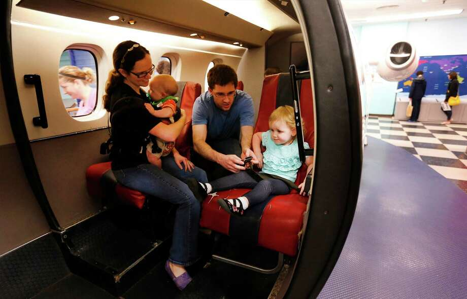 Penelope Ellis (left) and her husband, David, play inside the mock airplane with their two children Genevieve (right) and six-month-old Corbin at the San Antonio Children's Museum. on Saturday, Mar. 21, 2015. Some airlines appear poised to start charging more for the youngest (and often loudest) passengers. The museum celebrates its 20th anniversary and are on the verge of relocating to their new location with a new name, The DoSeum on Broadway. But before the move, the museum is auctioning off a majority of items from the Houston Street location. The airplane is one of many of the items placed for sale before their move to the new location. (Kin Man Hui/San Antonio Express-News) Photo: Express-News File Photo / ©2015 San Antonio Express-News