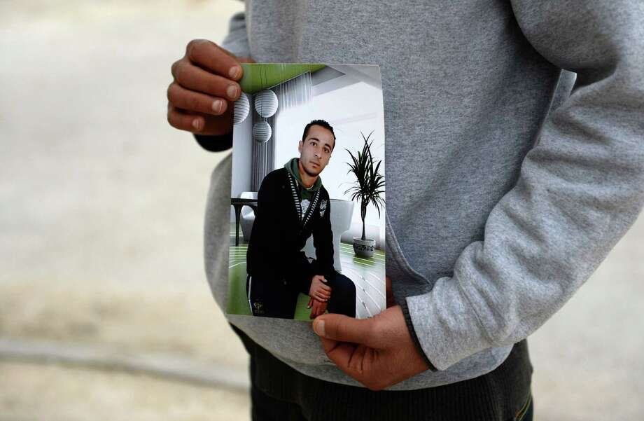 The brother of Yassine Laabidi (also spelled Abidi), one of Tunisia's Bardo museum assailants, shows a recent picture of him on March 21, 2015 in Omrane Superieur, a suburban neighbourhood of Tunis. Tunisia said the day before two gunmen who killed 21 people at its national museum trained at a militant camp in Libya.  AFP PHOTO / FADEL SENNAFADEL SENNA/AFP/Getty Images Photo: FADEL SENNA / AFP