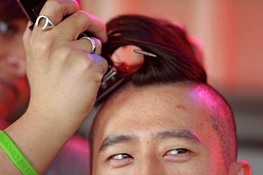"""Elise Lowe, volunteer of TGF Hair Salon, shaves the head of Sam Wu, of Houston, who raised $875 in his first year of participation in the St. Baldrick's Foundation head-shaving event to raise funds and awareness for lifesaving childhood cancer research at Little Woodrow's Saturday, March 21, 2015, in Houston, Texas. """"I heard about the foundation last year and it is a great organization,"""" said Wu. Photo: Gary Coronado, Houston Chronicle / © 2015 Houston Chronicle"""