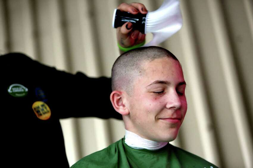 Stev3n Horowitt, volunteer of Salon Matos, puts the finishing touches on Zachary McElyea, 12, of Houston, who raised $340 in his second annual participation in the St. Baldrick's Foundation head-shaving event.