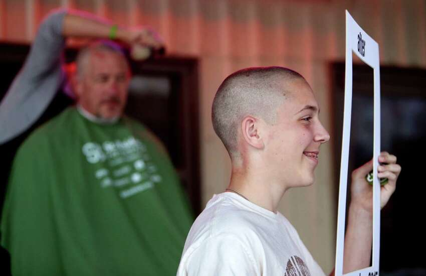 Zachary McElyea, 12, right, of Houston, has his 'after' photo taken while his dad Dan McElyea, gets his head shaved.