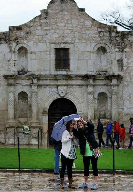 "Cousins Sydney Vernon (right) and Jennifer Goodwin from South Carlolina take a ""selfie"" in front of the Alamo before going on a tour on Saturday, Mar. 21, 2015. Light to moderate rain fell overnight and weather officials warned the area for possible urban and small stream flooding. (Kin Man Hui/San Antonio Express-News) Photo: Kin Man Hui,  Staff / ©2015 San Antonio Express-News"